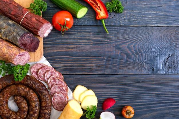 Wiele rodzajów kiełbasy, wędzonego sera, świeżych warzyw na drewnianym tle. skopiuj miejsce widok z góry. leżał płasko.