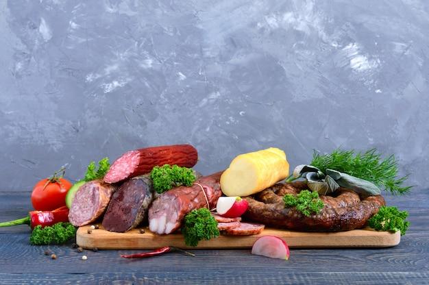 Wiele rodzajów kiełbasy, wędzonego sera, świeżych warzyw na drewnianym tle.