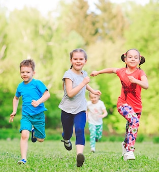 Wiele różnych dzieci, chłopców i dziewcząt biegających w parku w słoneczny letni dzień w zwykłych ubraniach