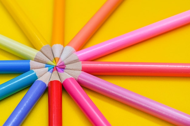 Wiele różnych kolorowych ołówków na żółtym tle. kolorowe kredki są ułożone w okrąg.