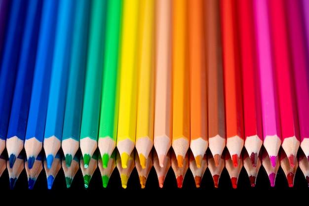 Wiele różnych kolorowych ołówków odzwierciedlenie na czarno