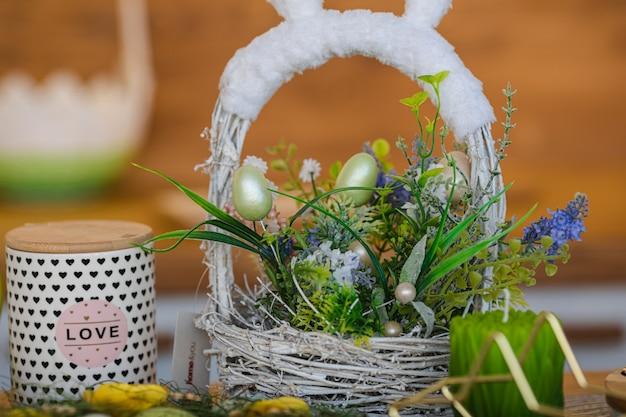 Wiele różnych kwiatów w koszyku w pobliżu uszu królika