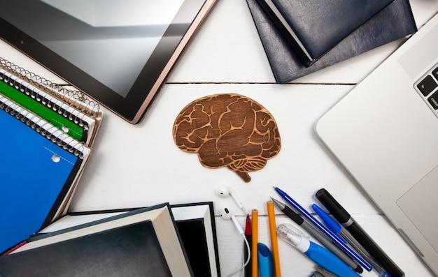 Wiele różnych materiałów edukacyjnych na drewnianym stole i mały drewniany mózg między nimi