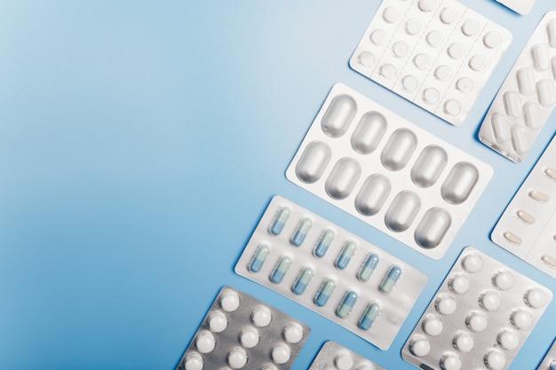 Wiele różnych opakowań tabletek na jasnoniebieskim tle. copyspace. skład ortogonalny.