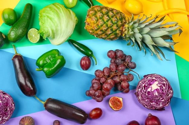 Wiele różnych owoców i warzyw na tle tęczy