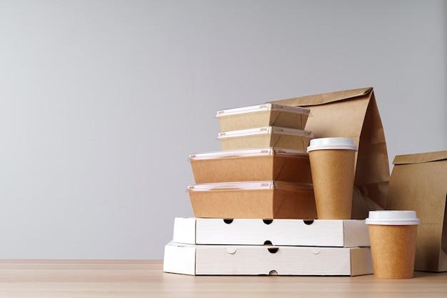 Wiele różnych pojemników na jedzenie na wynos, pudełka na pizzę, kubki do kawy i papierowe torby na jasnoszarym tle. dostawa jedzenia