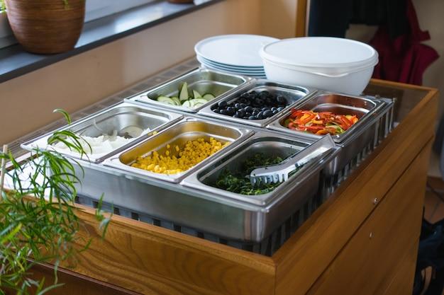 Wiele różnych posiekanych warzyw w metalowych pojemnikach