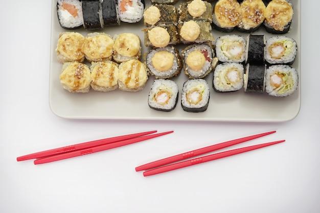 Wiele różnych pysznych japońskich rolek sushi na talerzu i czerwone patyczki do bułek