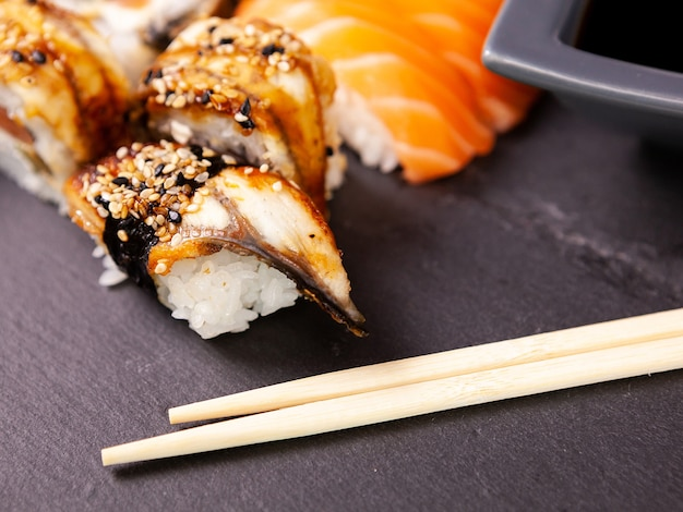 Wiele różnych rolek sushi na czarnym kamiennym tle w studio fotograficznym