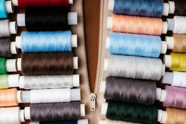 Wiele różnych rolek z gwintami, układanie na płasko, widok z góry. kolorowe nici, zbliżenie, jasne tło. koncepcja cięcia i szycia odzieży. akcesoria do robótek ręcznych.