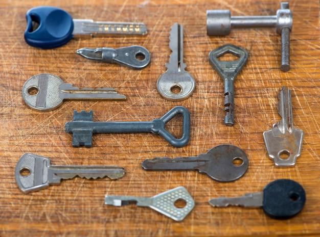 Wiele różnych starych wielokolorowych metalowych antycznych kluczy vintage o różnych kształtach na tle drewniany stół porysowany.