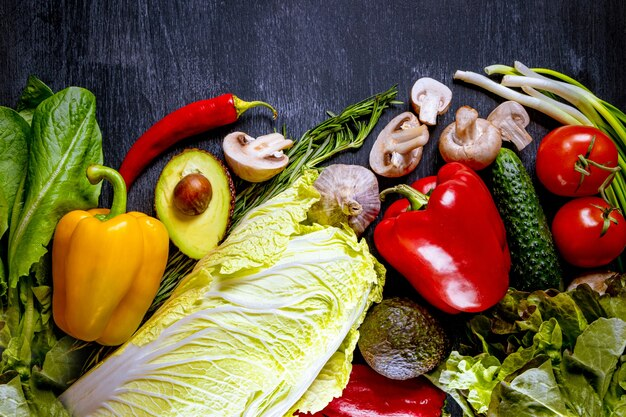 Wiele różnych świeżych warzyw na czarnej powierzchni z wolnym miejscem na tekst.