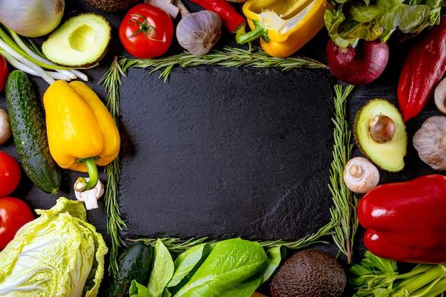 Wiele różnych świeżych warzyw na czarnym tle z wolnym miejscem na tekst.