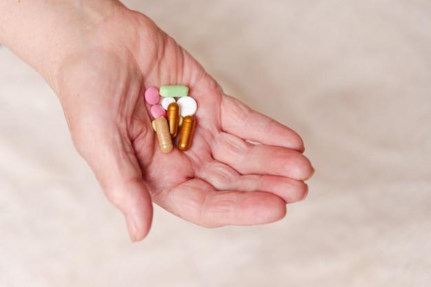 Wiele różnych tabletek w ręce osoby starszej.