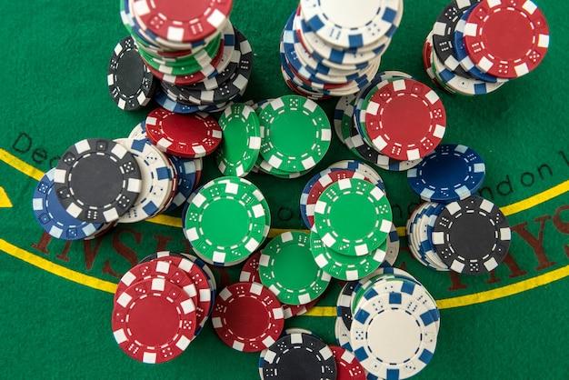 Wiele różnych żetonów do pokera kosztuje na stole do gry. duży zakład na grę na zielonym polu sukna