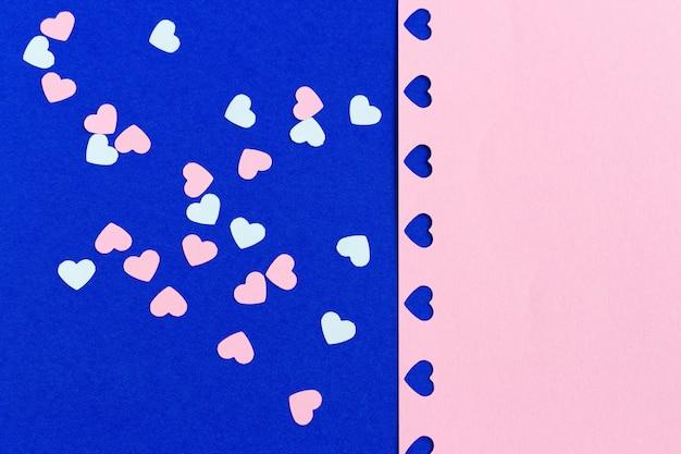 Wiele różowi i biali papierowi serca kształtujący confetti na błękitnym tle.