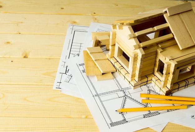 Wiele rysunków do budowy, ołówków i małego domu na drewnianym tle.