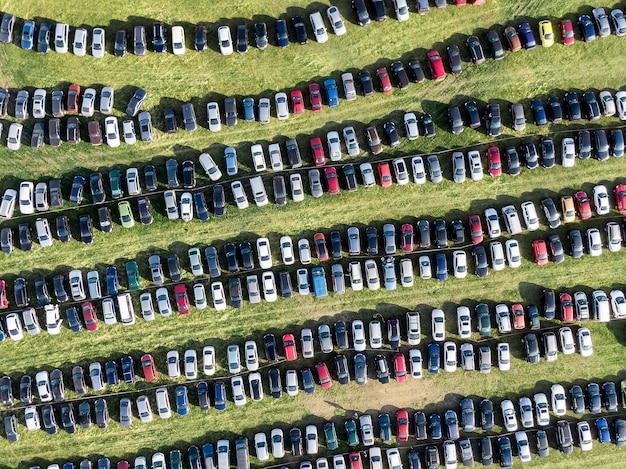 Wiele samochodów zaparkowanych na polu.