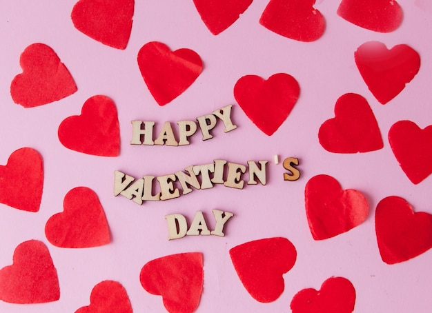 Wiele serc z napisem szczęśliwych walentynek na różowym tle.