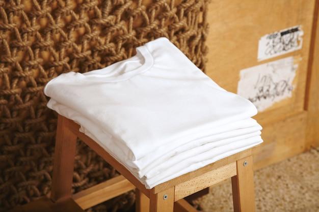 Wiele składanych białych koszulek bawełnianych basic prezentowanych w rustykalnym wnętrzu