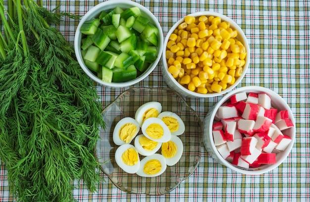 Wiele składników sałatki (kukurydza, ogórek, mięso kraba, jaja przepiórcze) na jasnym tle. widok z góry