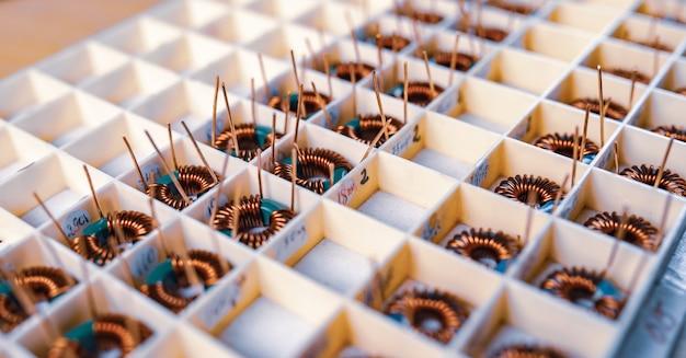 Wiele skręconych miedzianych cewek leży w przedziałach do dalszej produkcji sprzętu elektronicznego. koncepcja fabryki do produkcji sprzętu medycznego