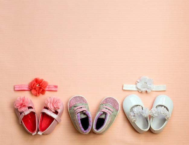 Wiele śliczny dziecko but umieszczający na różowym tle, odgórny widok