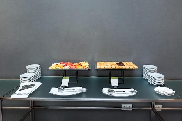Wiele słodkich babeczek i pokrojone owoce na stole na kawę w biurze.