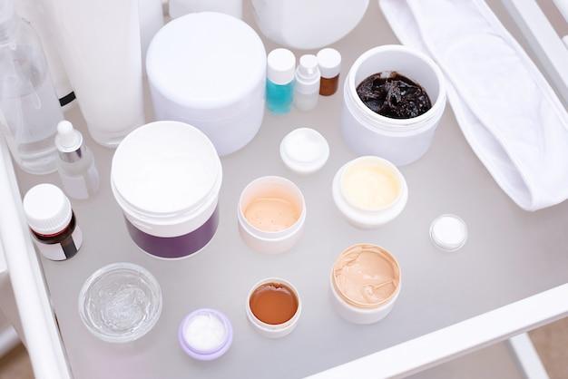 Wiele słoików z różnymi kremami na szklanym stole w salonie kosmetycznym, koncepcja pielęgnacji skóry twarzy, z bliska.