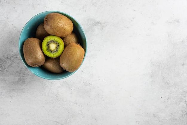 Wiele smacznych owoców kiwi na niebieskiej misce.