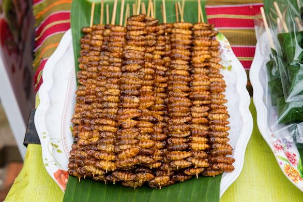 Wiele smażonych pałeczek poczwarki jedwabników jest sprzedawanych na targu ulicznym w tajlandii. owady to pokarmy wysokobiałkowe.