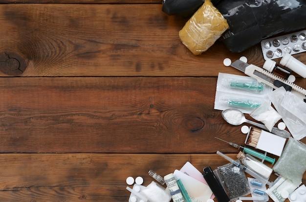 Wiele środków odurzających i urządzeń do przygotowywania narkotyków leży na starym drewnianym stole w tle