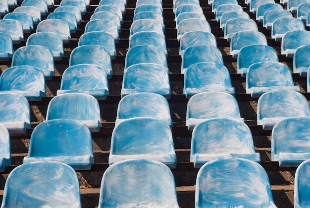 Wiele starych niebieskich krzeseł na stadionie piłkarskim