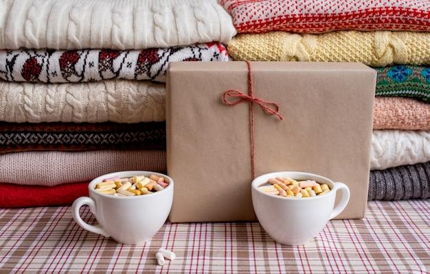 Wiele swetrów i pulowerów w różnych kolorach złożonych w dwóch stosach z pudełkiem prezentowym i dwiema filiżankami kawy.