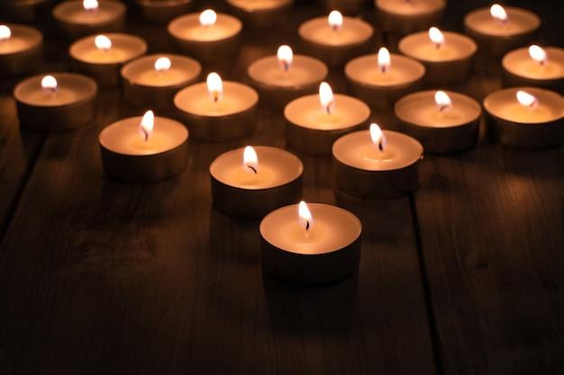 Wiele świec pali się w nocy. abstrakcyjne tło. ścieśniać