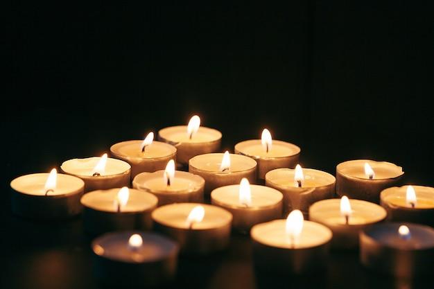 Wiele świec płonących w nocy. wiele płomieni świec świecące na ciemnym tle