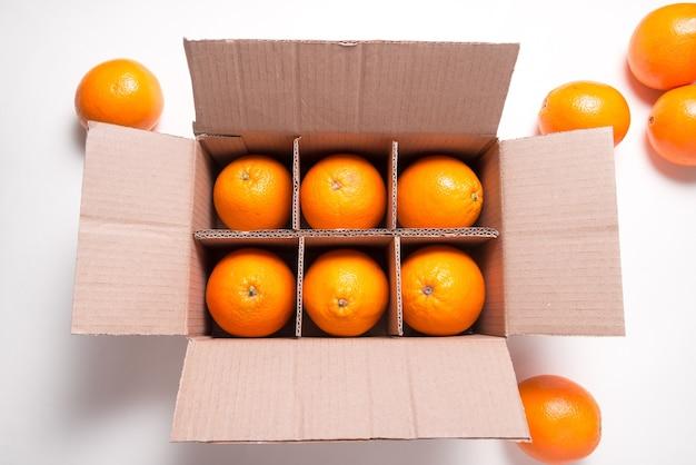 Wiele świeżych owoców cytrusowo-pomarańczowych w kartonowym pudełku
