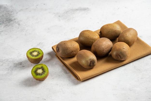 Wiele świeżych owoców kiwi na brązowym obrusie.