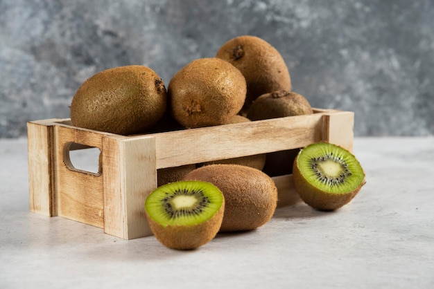 Wiele świeżych owoców kiwi na drewnianym koszu.