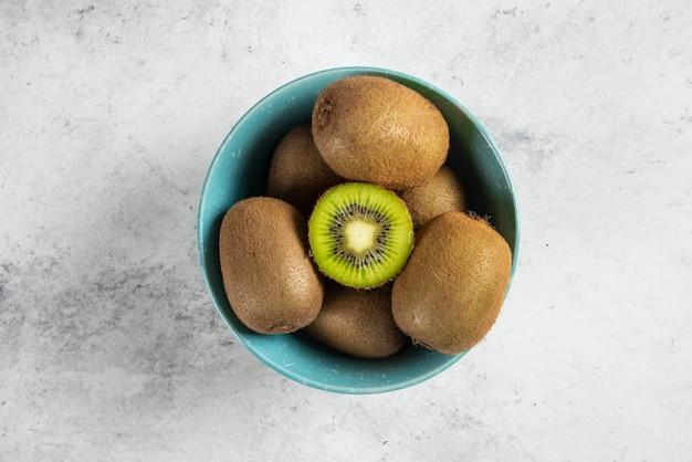 Wiele świeżych owoców kiwi na niebieskiej misce.