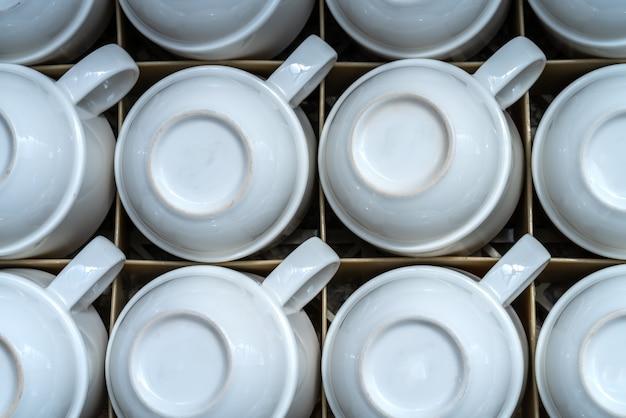 Wiele takich samych białych kubków na napoje, kawę lub herbatę. stać do góry nogami w szufladzie.