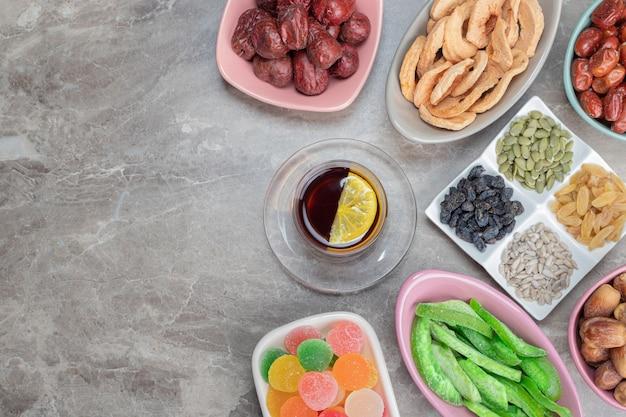 Wiele talerzy suszonych owoców, marmolady, pestek słonecznika z herbatą.