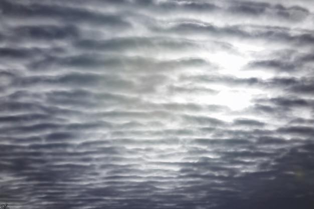 Wiele teksturowanych chmur na niebieskim niebie ze światłem słonecznym