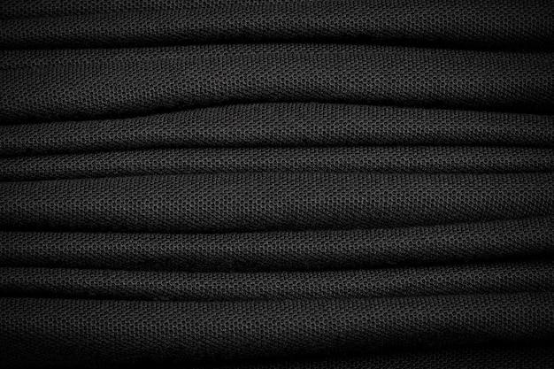 Wiele tła czarnej koszuli. ciemny materiał tekstylny.