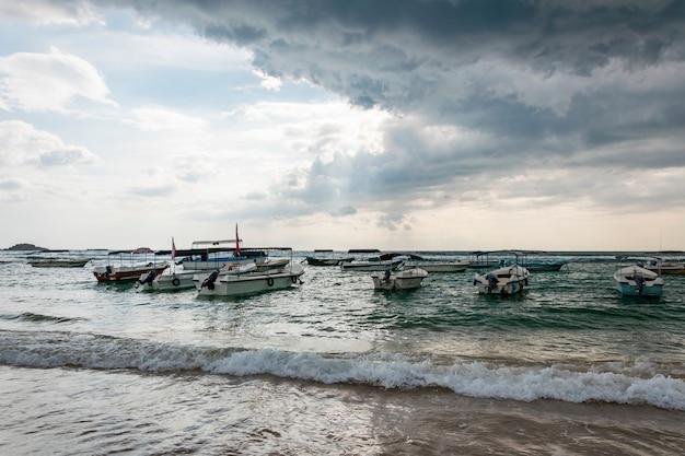Wiele tradycyjnych łodzi i jachtów nad morzem lub oceanem. zbliżająca się burza tropikalna z deszczem i ciemnymi chmurami deszczu na niebie i przebijającym się przez nie słońcem