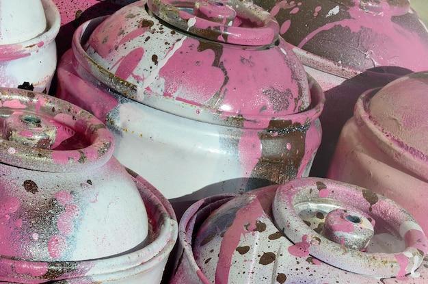 Wiele używanych różowych metalowych zbiorników z farbą do rysowania graffiti