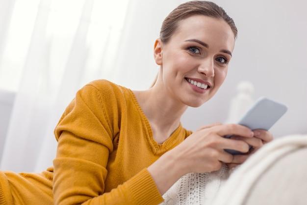 Wiele wiadomości. atrakcyjna przezabawna ładna kobieta trzymając telefon, patrząc na kamery i uśmiechając się