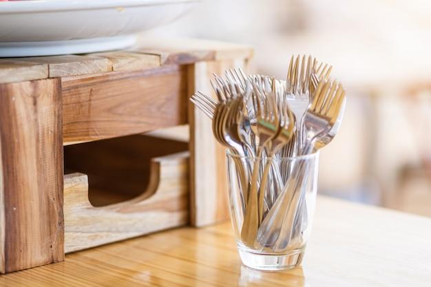 Wiele widelców umieszcza się w szklance na dekoracji stołu