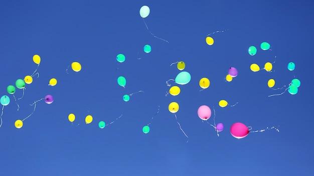 Wiele wielobarwnych balonów latających w błękitne niebo. dekoracje świąteczne