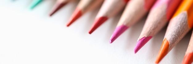 Wiele wielobarwnych ołówków leżących na białym tle zbliżenia